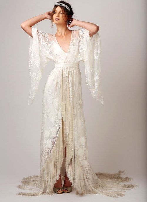18 Romantic Bomemian Chic Summer Wedding Dresses for The Modern Boho Princess: A dress for a true bohemian princess. Long lace wrap wedding dress for summer with sexy V-neck, bath sleeves and fringed hem skirt