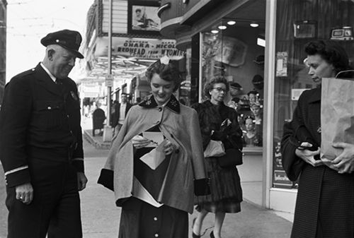 A police officer handing out Valentines to strangers, c. 1955