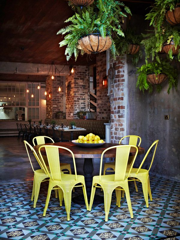 The Grounds at Alexandria - I love the rustic textures and colour of the brick, concrete and tile.  The jolt of yellow in the chairs brings a lift and a smile as does the retro hanging basket with fern.