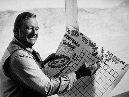 "John Wayne Betting on USC/UCLA football game, on location for ""Chisum,"" Warner Bros. 1969."