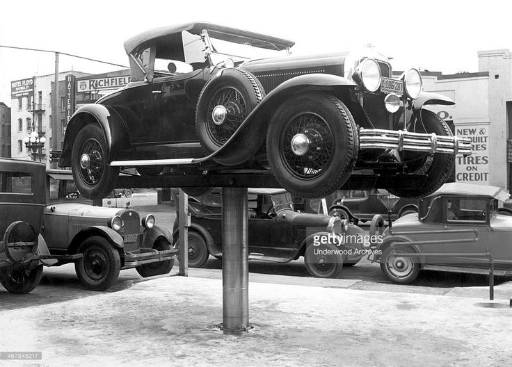 An automobile perched on an Elder Auto Lift at an outdoor repair shop, Los Angeles, California, 1928.