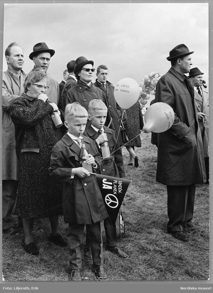 Fredsdemonstration på Gärdet i Stockholm. En grupp människor har samlats, två finklädda pojkar i förgrunden. 1960-tal.
