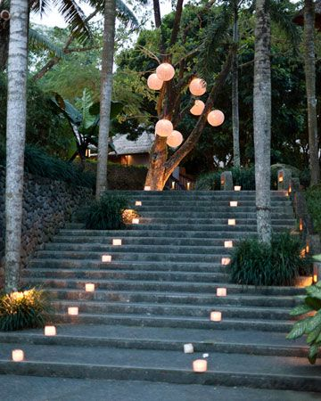 Candles light up the stairs, and paper lanterns shine in the trees