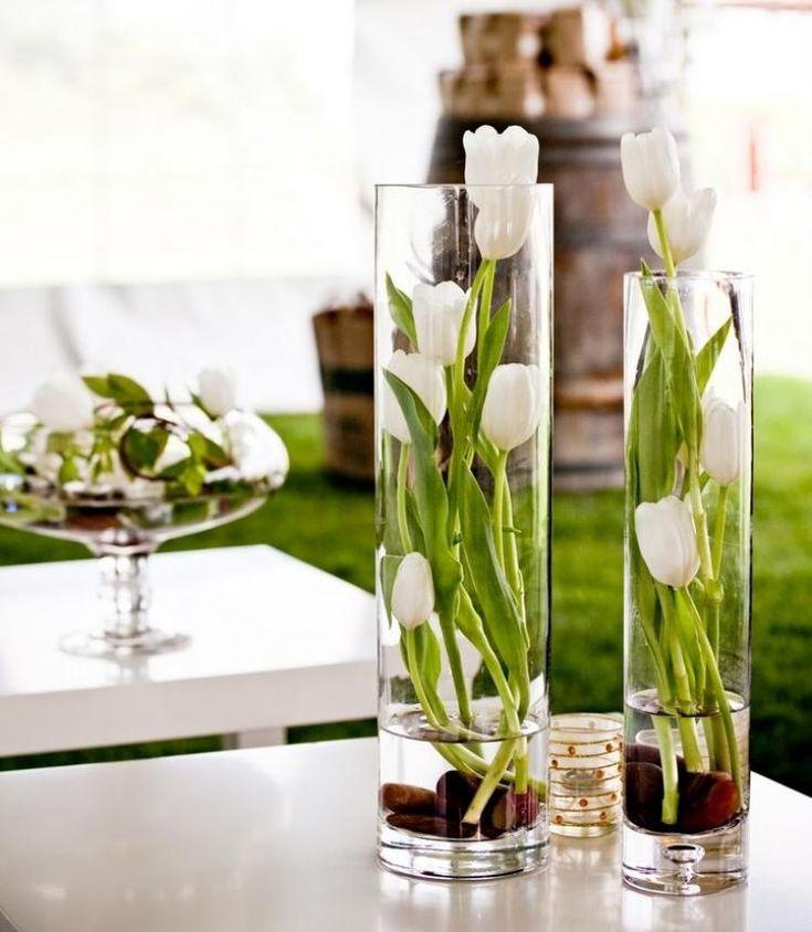 weiße Tulpen in hohen Glasvasen - Kies im Wasser
