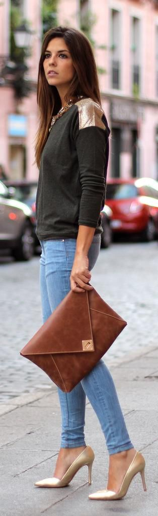 forest green sweater with patches on shoulders, with oversized soft brown clutch, gold heels and light wash jeans