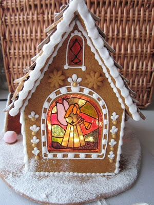 gingerbread house lit, with a beautiful stained glass window.