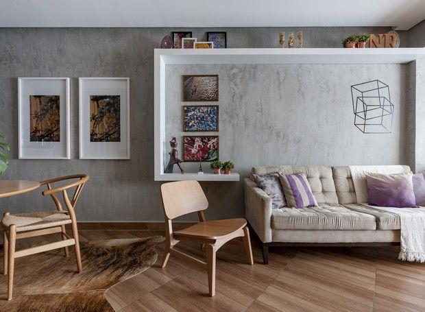 SALA | A parede foi pintada com tinta com efeito marmorato. A poltrona Leo, da Tok&Stok, acomoda mais um convidado e divide visualmente o jantar do estar. O sofá, da Etna, já era dos clientes e foi mantido no projeto. Na parede, prateleiras, da Etna, limitam o espaço para o sofá e emolduram fotos tiradas por Nadia durante viagens