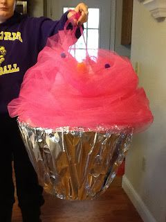 Supplies  base for cupcake -a thrift store lampshade, cardboard or cut out the bottom of a round laundry basket, shoulder straps -pink ribbon, base for frosting -light pink t-shirt, frosting -tulle, sprinkles -craft pom poms, cupcake liner tin foil.