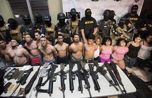 Honduran police with alleged members of the Barrio 18 gang who were found in possession of illegal weapons in San Pedro Sula. The group is being held in connection with the death of Igor Padilla, a journalist who was reportedly shot dead this week by men in police uniform.