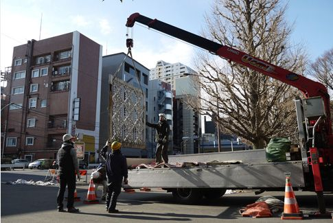 A door from the main gate is suspended from a crane, to send it off for restoration.