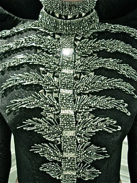 safety pins and studs that from afar look like a leafy ribcage