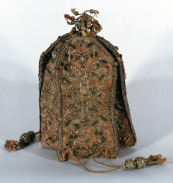 Purse, ca. 1600 Purse with drawstring top and tasseled bottom, made up of six shield-shaped panels of figured silk sewn together; the seams are covered with gilt wire. Each panel is ornamented with embroidery in couched bullion and metal thread embroidery. Secured at the top with silk cords ending in tassels with braided metallic heads.