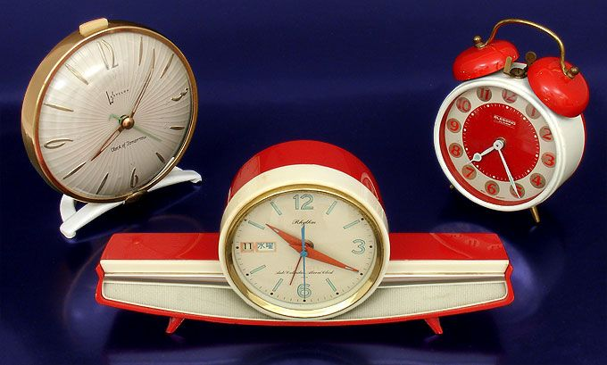 """Upper left is, the wind-up Clock of Tomorrow by Westclox (1955, USA).  Center is a delightful clock that reminds me of a 1950s Chevrolet emblem. It's a wind-up Rhythm """"Auto Calendar Alarm Clock"""" (c.1958, Japan). On the right is the fun Blessing wind-up alarm clock from West Germany, c.1960."""