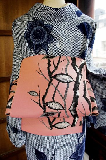 ほのかにスモークがかった淡いピンク色の地に、黒とシルバーで織り出された樹木模様がモダンな単帯です。