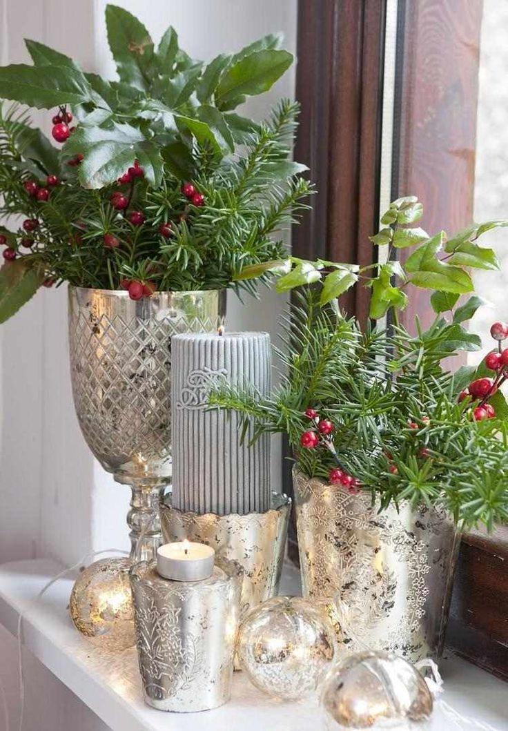 arrangement de baies rouges, feuilles de houx et branchettes de sapin en vases argentés pour Noël