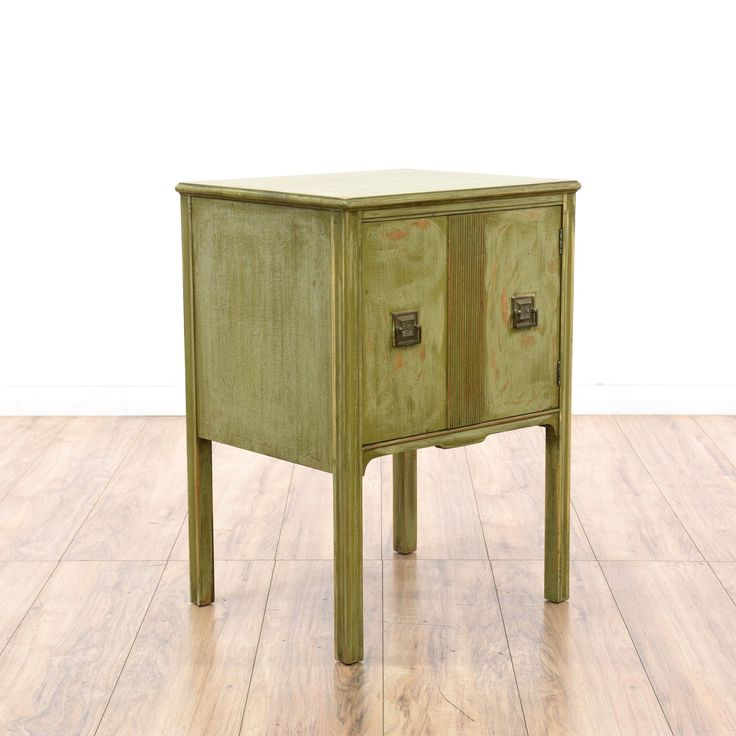 This asian cabinet table is featured in a solid wood with a distressed sage green paint finish. This hutch cabinet has tall straight legs with an interior cupboard and unique square metal hardware. Eye catching console great for a small entryway!  #asian #storage #cabinet #sandiegovintage #vintagefurniture