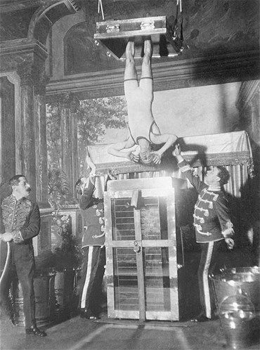 Magician Harry Houdini performs his famous Chinese Water Torture Cell escape in California in 1913. Houdini, with his ankles secured in stocks, was submerged in the glass tank full of water and locked in place in full view of the audience. He was the only person during his lifetime to pull off the escape.