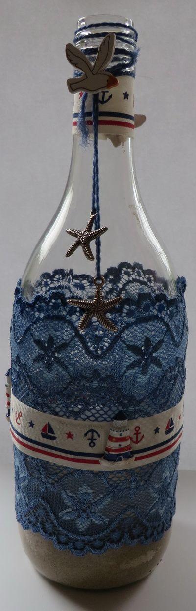 Wijnfles met blauw kant, lint, vuurtorentjes, vogeltjes, zilverkleurige bedeltjes en in de fles zand met plastic schelpjes. € 4,95