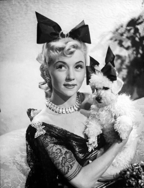 A delightfully charming portrait of Gloria Grahame and her adorable canine companion.