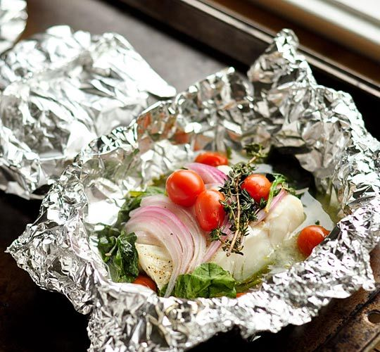 Fish Oven Packets  1 pound fish fillets, about 1-inch thick  2 large handfuls baby spinach leaves  1 quarter red onion, thinly sliced  20 or so cherry tomatoes  4 sprigs fresh thyme  1/2 lemon, cut into 2 wedges  Salt and pepper  Olive oil or butter    Preheat the oven to 400°F.