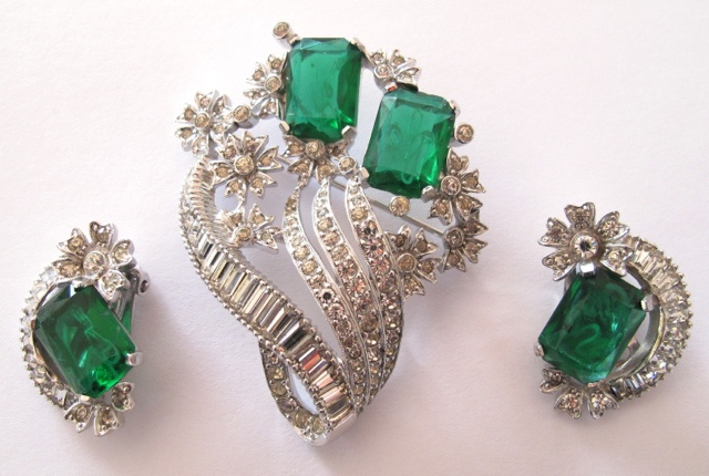 """A truly great """"real look"""" set that is becoming harder and harder to find. Bright clear rhinestones and large emerald complete with inclusions are set in rhodium plated metal. This set is in PRISTINE condition with no dark stones and no signs of wear. All pieces are signed Jomaz. Pin is 2¼"""" by 2"""". Clip on earrings are 1"""".   #96"""