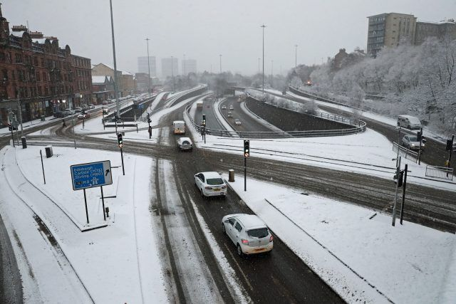 (Andrew Milligan/PA) Snowfall Hits UK As 'Severe Weather' Rolls Across Country: Cars drive in the snow-covered Charing Cross area of Glasgow