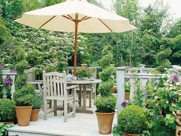 Spiral topiaries and boxwoods, all in pots, frame the entrance to this open deck.