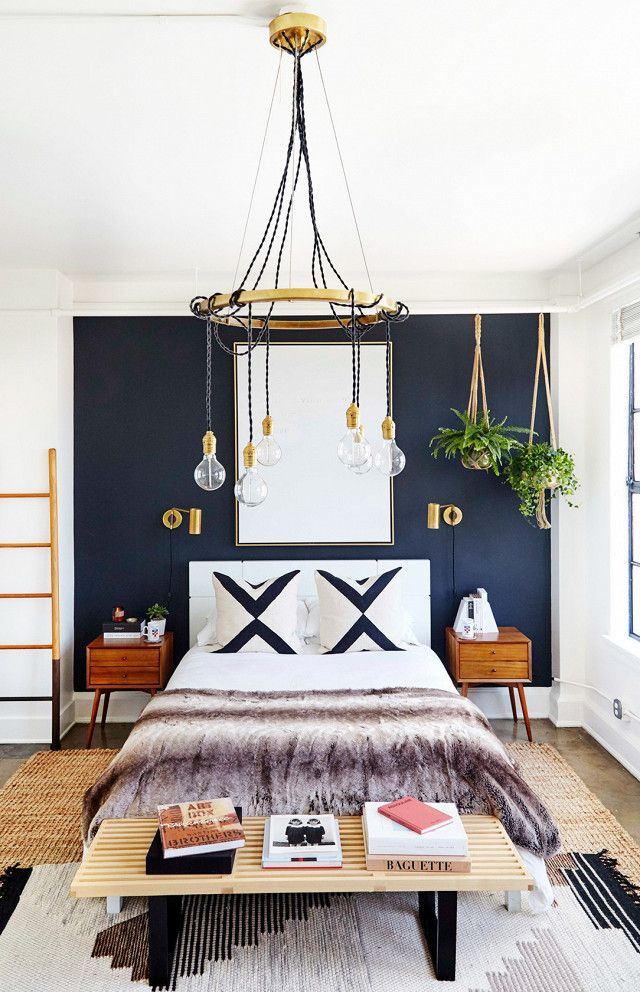 Glam Bedroom With A Black Contrast Wall A Chandelier And Layered Rugs