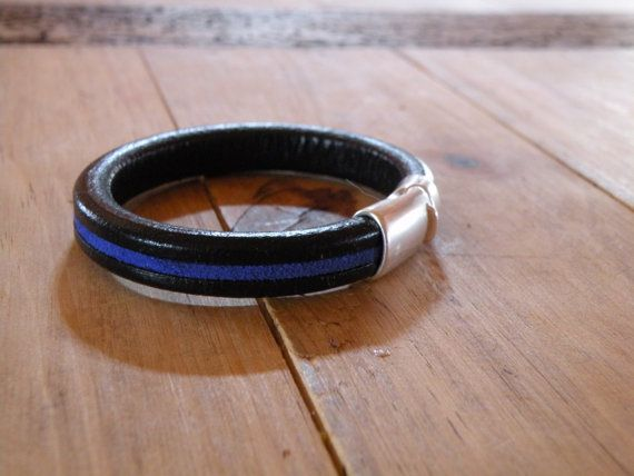 Thin Blue Line bracelets dont get any better than this! Hand MADE IN AMERICA out of high quality European leather. The attractive clasp is magnetic, easy to put on and take off, yet holds securely. The metal is hypo-allergenic. SUPPORT AMERICAS LAW ENFORCEMENT OFFICERS!  Please indicate your WRIST MEASUREMENT when indicating size. How to measure your wrist: Wrap a flexible measuring tape or string around your wrist right above the wrist bone. Round up to the nearest quarter inch. Women…
