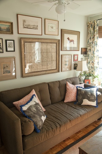 Arrangement over sofa--Symmetrical anchor of large center piece flanked on bottom line by two equal pictures, then the wall more casually filled in, extending over side tables.