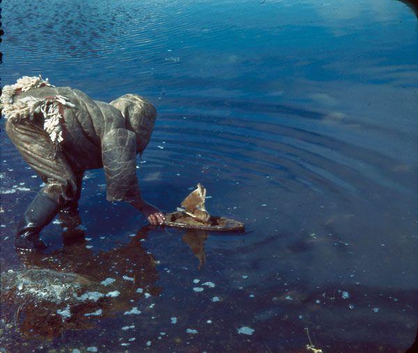 Inuit child sailing his toy boat with caribou skin sails / Un enfant inuit fait voguer son bateau avec des voiles en peau de caribou   by BiblioArchives / LibraryArchives