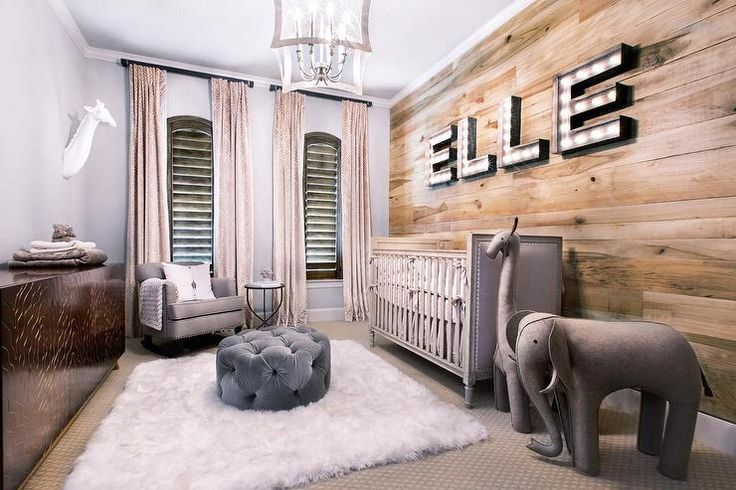 Rustic nursery features an accent wall clad in planks lined with marquee light spelling out the name: ELLE, placed above a gray nailhead crib, Restoration Hardware Baby & Child Marcelle Crib, next to an Oversized Wool Felt Elephant and Giraffe.