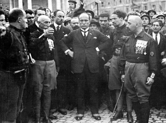 Ο Ιταλός φασίστας ηγέτης Μπενίτο Μουσολίνι, στο κέντρο, με τα χέρια στους γοφούς, με μέλη του φασιστικού κόμματος, στη Ρώμη, 28 Οκτωβρίου 1922, μετά την πορεία τους προς την πόλη. Η πορεία αυτή ήταν μια πράξη εκφοβισμού, όπου χιλιάδες φασίστες Μελανοχίτωνες κατέλαβαν στρατηγικές θέσεις στο μεγαλύτερο μέρος της Ιταλίας. Μετά την πορεία, ο βασιλιάς Emanuelle ΙΙΙ ζήτησε από τον Μουσολίνι να σχηματίσει νέα κυβέρνηση, ανοίγοντας το δρόμο προς μια δικτατορία. (ΦωτογραφίαAP)