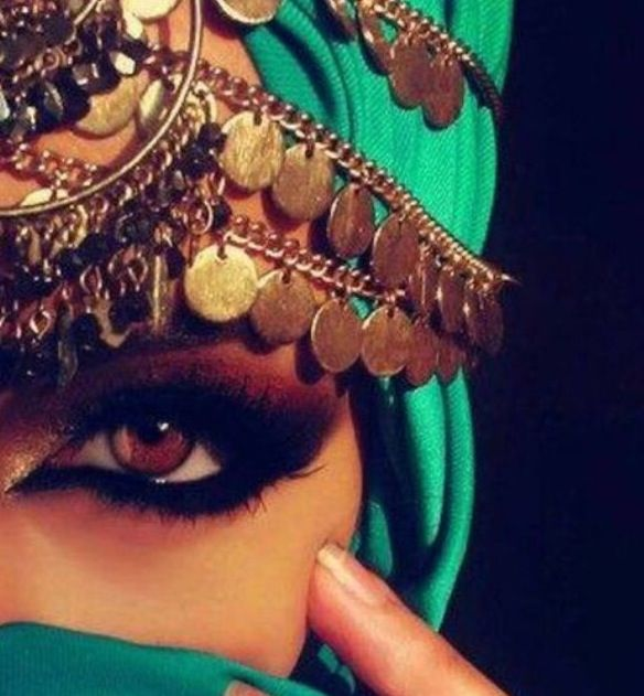 Arabian inspired bridal eye makeup. Heavy eyeliner and coin headpiece.