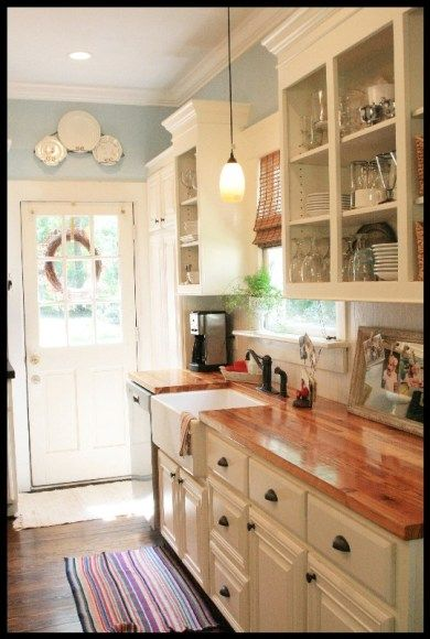 Apron sink, wood counters, white cupboards with crown molding.  Lovely blue walls!