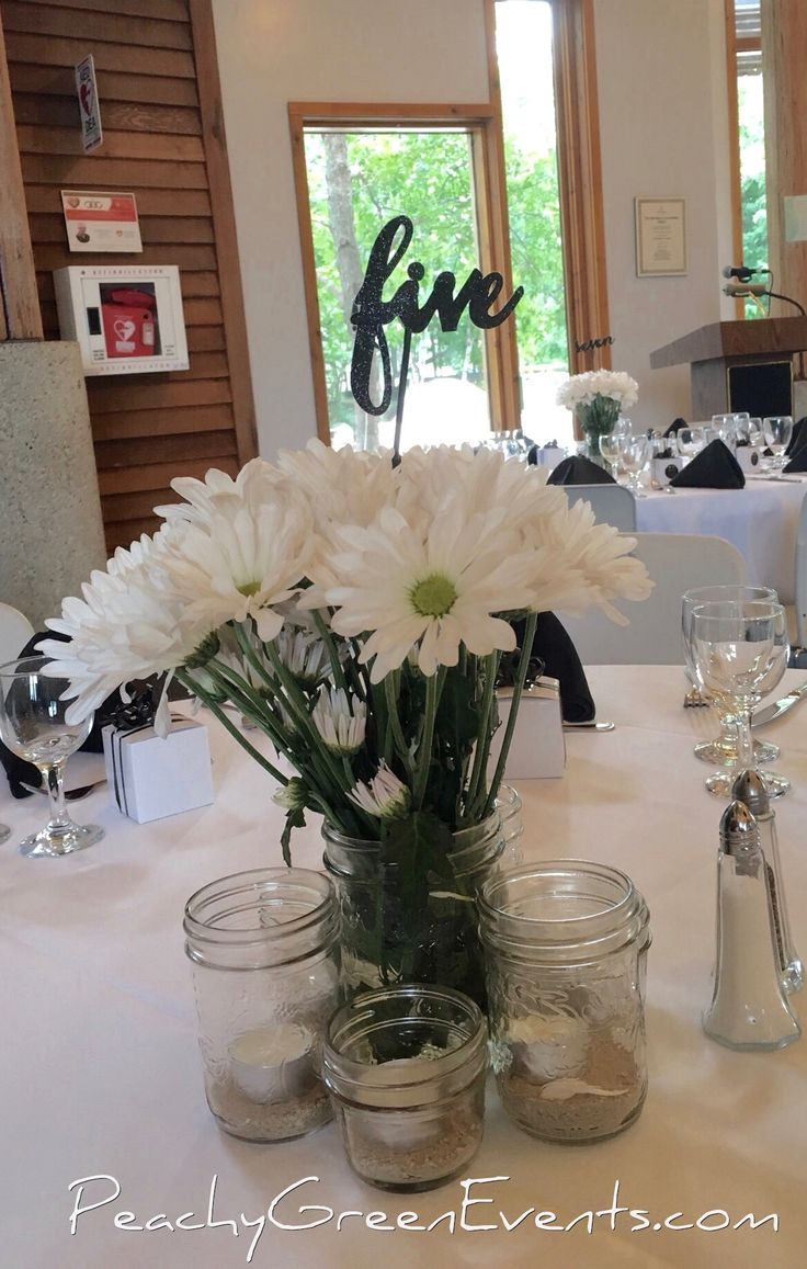 Daisies and mason jar candles with written table number centre piece at Fort Whyte Alive in Winnipeg. Decor rented from and set up by Peachy Green Events.