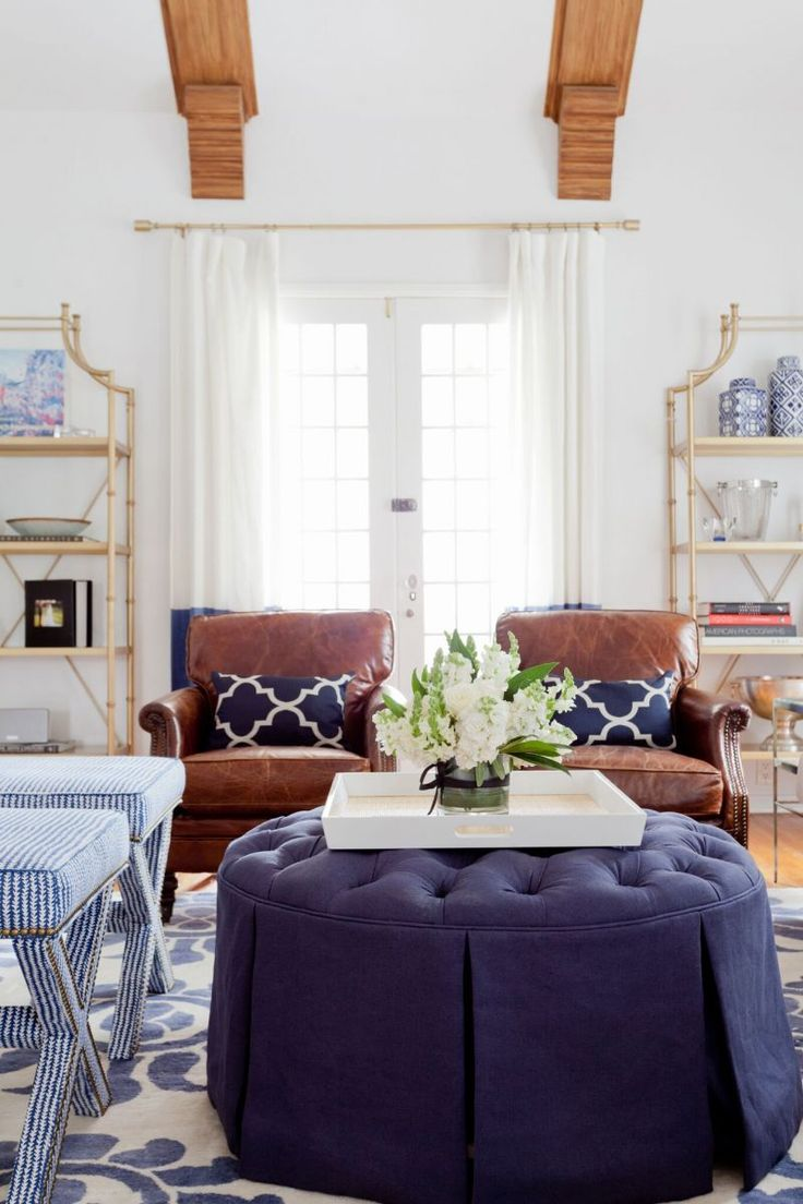 10 Commandments to Designing Your Living Room #theeverygirl | lovely blue and white young trad living room with white walls, white drapes, and brown leather chairs for some oomph