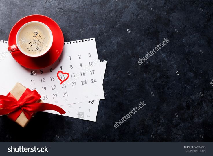 Valentines day greeting card. Red coffee cup and gift box over february calendar on stone table. Top view with space for your greetings