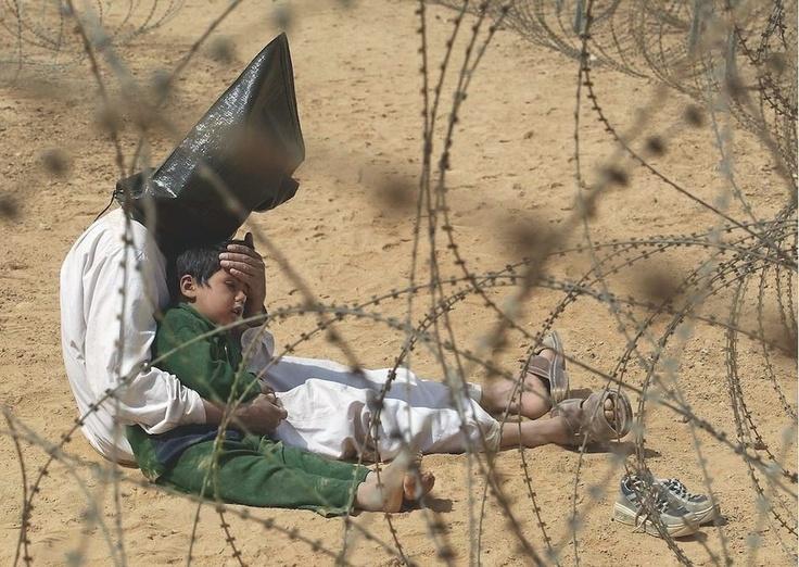 2003  Un hombre iraquí consuela a su hijo de cuatro años de edad en un centro de detención para los prisioneros de guerra, en el campamento base de la División Aerotransportada 101 del Ejército de EE.UU. cerca de An Najaf. El muchacho estaba aterrado, por órdenes, su padre fue encapuchado y esposado. Un soldado cortó las esposas de plástico para que el hombre pudiera consolar a su hijo. Se colocaron bolsas sobre las cabezas de los detenidos, ya que eran más rápidas de aplicar que las vendas