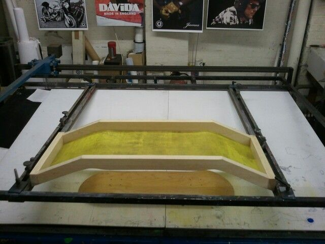 Special-built screen for silk screen printing a skateboard.