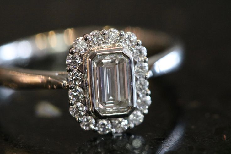 Stunning emerald cut diamond engagement ring with diamond halo set in white gold. Finance available on all items over £500, subject to status.