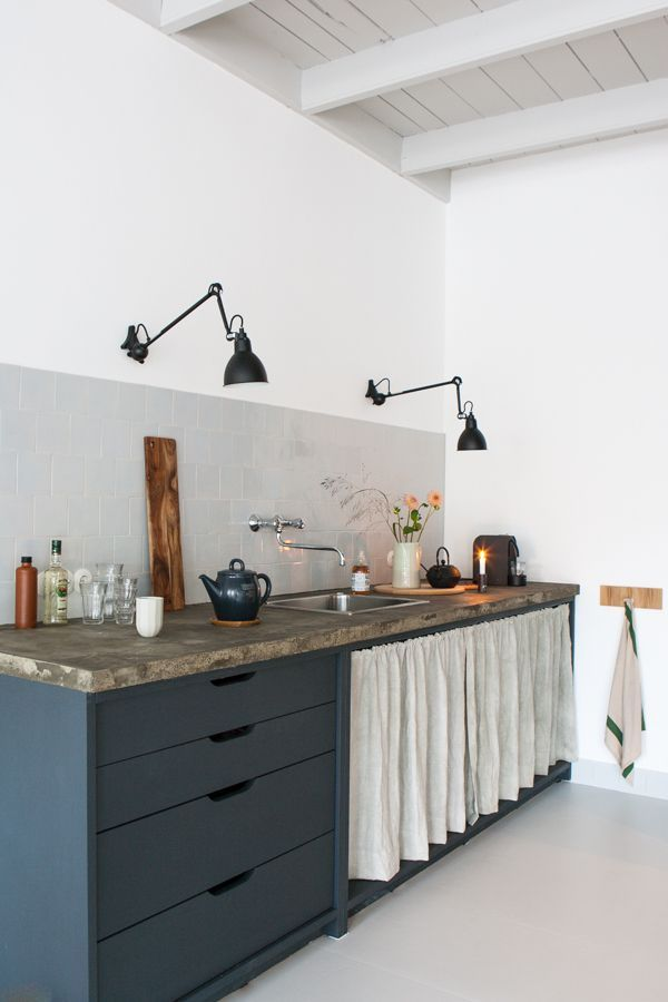 modern kitchen with concrete counters, charcoal cabinets, and industrial lighting