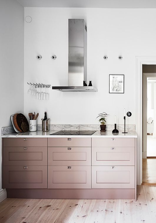 Interesting play of warm and cool tints, pink cabinets, chrome extractor hood, marble worktop