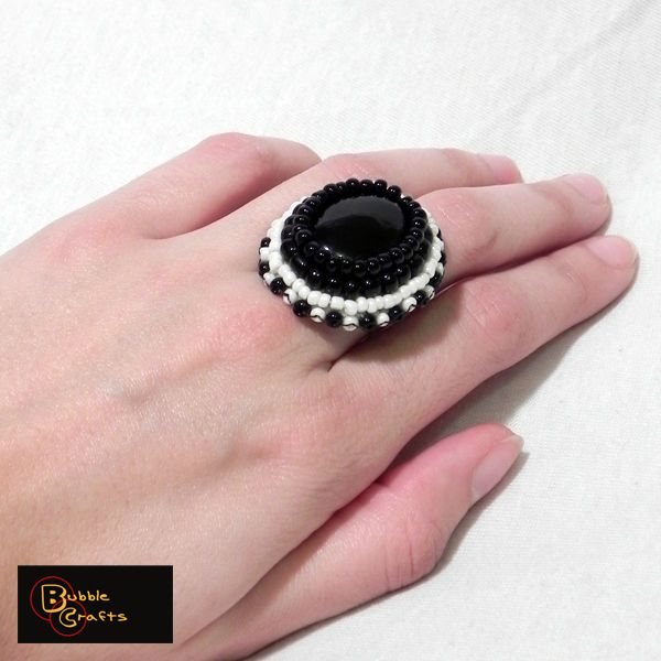 Bead embroidered ring made of black and white sand beads and a large black agate in the center