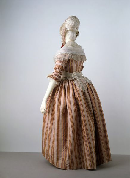 """In the 1770s a new style of wearing gowns was introduced, called a polonaise. Using buttons and loops, the skirt of the gown was draped up to create a swathed effect at the back. Also introduced during this decade were a range of striped fabrics, often in a complex arrangement of colours with both sharp and shaded edges, as seen in this example...This dress is shown with the skirt undraped, showing how the wearer had the choice of wearing the gown without the polonaise drapery."""