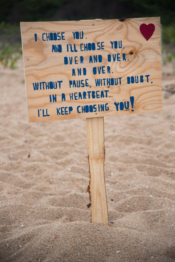 Love this adorable love quote sign for a beach proposal!
