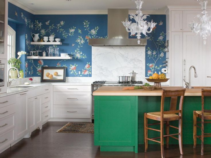 A white kitchen doesn't have to be all white. Here, designer Andrea Schumacher swapped upper cabinets for just two small shelves so the fanciful floral wallpaper is the star. For contrast, she chose an emerald green tone from the wallpaper to paint the kitchen's island.