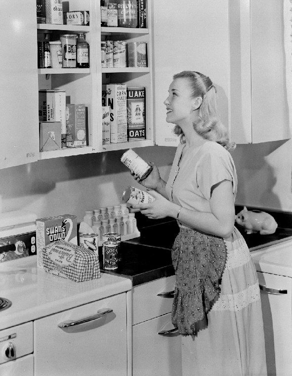 A woman putting cans away in her kitchen cupboard, 1852. #vintage #1950s #homemaker