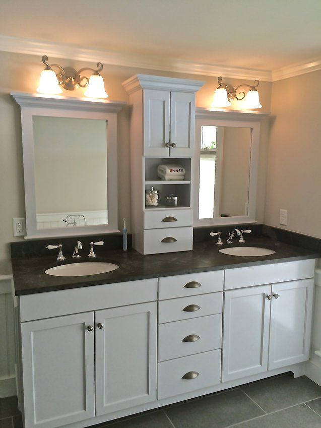 a frameless full overlay door and drawer bathroom vanity complete with a tower for extra storage and a mirror over each sink