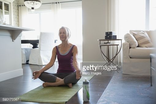 Stock Photo : Serene senior woman meditating lotus position living room